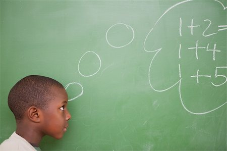 Schoolboy thinking about additions in front of a blackboard Stock Photo - Budget Royalty-Free & Subscription, Code: 400-05895621