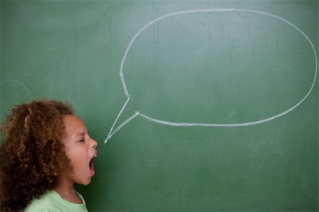 Schoolgirl screaming a speech bubble in front of a blackboard Stock Photo - Budget Royalty-Free & Subscription, Code: 400-05896425