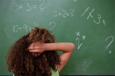 Schoolgirl thinking about mathematics while scratching the back of her head in front of a blackboard Stock Photo - Budget Royalty-Free & Subscription, Code: 400-05896431