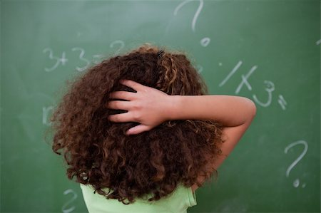 Schoolgirl thinking about algebra while scratching the back of her head in front of a blackboard Stock Photo - Budget Royalty-Free & Subscription, Code: 400-05896484