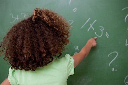 Schoolgirl pointing at an addition on a blackboard Stock Photo - Budget Royalty-Free & Subscription, Code: 400-05896486