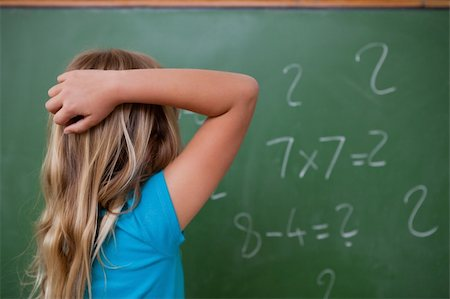 Little schoolgirl thinking while scratching the back of her head in front of a blackboard Stock Photo - Budget Royalty-Free & Subscription, Code: 400-05896497