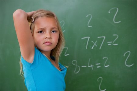Schoolgirl thinking while scratching the back of her head in front of a blackboard Stock Photo - Budget Royalty-Free & Subscription, Code: 400-05896498