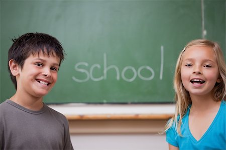 Happy pupils posing together in front of a chalkboard Stock Photo - Budget Royalty-Free & Subscription, Code: 400-05896515