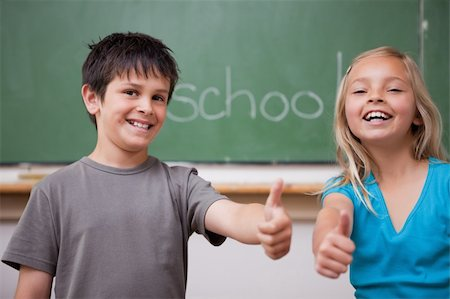 Happy pupils posing with the thumb up in a classroom Stock Photo - Budget Royalty-Free & Subscription, Code: 400-05896516