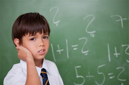Confused schoolboy thinking while scratching the back of his head in a classroom Stock Photo - Budget Royalty-Free & Subscription, Code: 400-05896551
