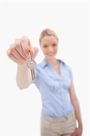 finger holding a key - Key being handed over by woman against a white background Stock Photo - Budget Royalty-Free & Subscription, Code: 400-05898826