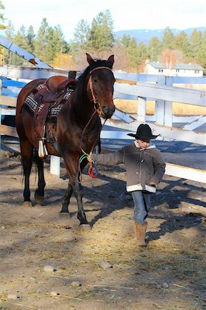 Young boy leading his horse in the riding pen Stock Photo - Budget Royalty-Free & Subscription, Code: 400-05890834