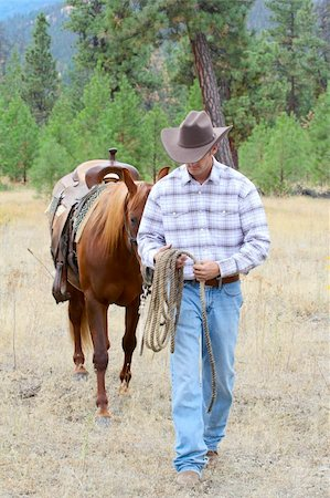 Young cowboy leading his horse through the field Stock Photo - Budget Royalty-Free & Subscription, Code: 400-05890876