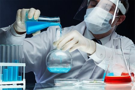 Scientist pouring fluid substances from one beaker into another Stock Photo - Budget Royalty-Free & Subscription, Code: 400-05914477