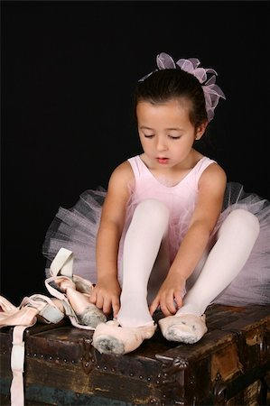 Cute little brunette girl trying on ballet pointe shoes Stock Photo - Budget Royalty-Free & Subscription, Code: 400-05911840