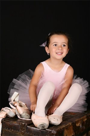 Cute little brunette girl trying on ballet pointe shoes Stock Photo - Budget Royalty-Free & Subscription, Code: 400-05911841