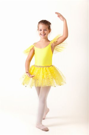 Smiling little ballerina exercising, studio shot on white background Stock Photo - Budget Royalty-Free & Subscription, Code: 400-05924060