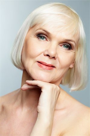 Woman of senior age holding her head gracefully and looking at camera with a smile Stock Photo - Budget Royalty-Free & Subscription, Code: 400-06064672