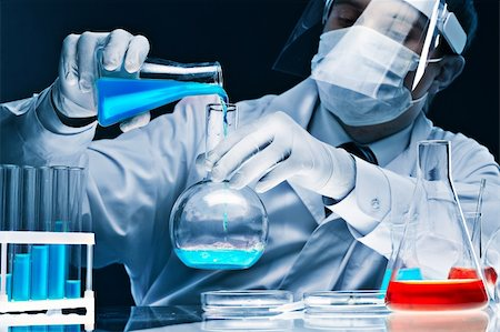 Masked male scientist mixing bright blue substances in glassware Stock Photo - Budget Royalty-Free & Subscription, Code: 400-06067873