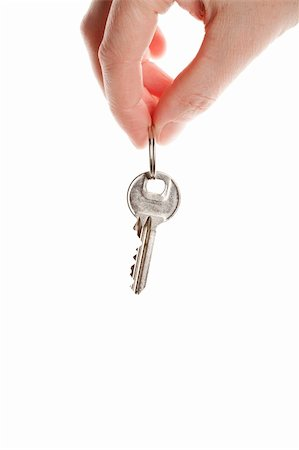 finger holding a key - Hand and key isolated on white background Stock Photo - Budget Royalty-Free & Subscription, Code: 400-06069124