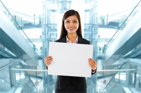 Mixed race Asian businesswoman holding a white board standing inside modern building. Stock Photo - Budget Royalty-Free & Subscription, Code: 400-06087203