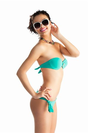 cute sexy brunette in green bikini with white sunglasses and curly hair style over white, she is turned in profile with right hand on the hip, she looks in to the lens and smiles Stock Photo - Budget Royalty-Free & Subscription, Code: 400-06080832