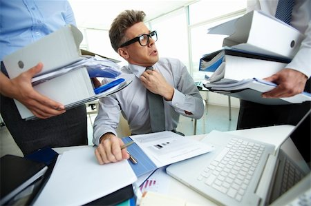 Shocked accountant looking at huge piles of documents held by his partners Stock Photo - Budget Royalty-Free & Subscription, Code: 400-06094827