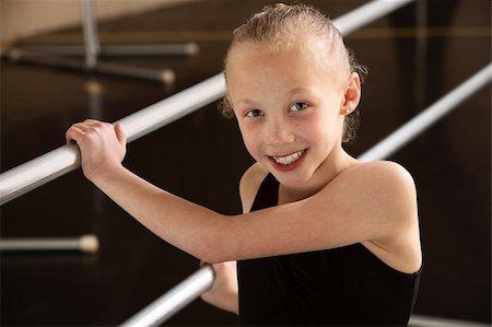 Smiling ballerina girl holding balance bars in dance studio Stock Photo - Budget Royalty-Free & Subscription, Code: 400-06097048