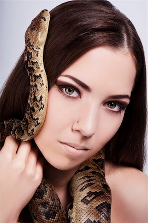 beautiful brunette girl with a snake around her head stares at the viewer Stock Photo - Budget Royalty-Free & Subscription, Code: 400-06091490
