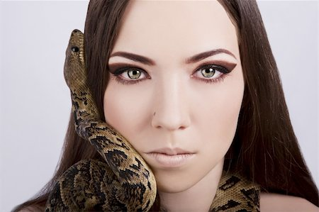 beautiful brunette girl with a snake around her head stares at the viewer Stock Photo - Budget Royalty-Free & Subscription, Code: 400-06091491