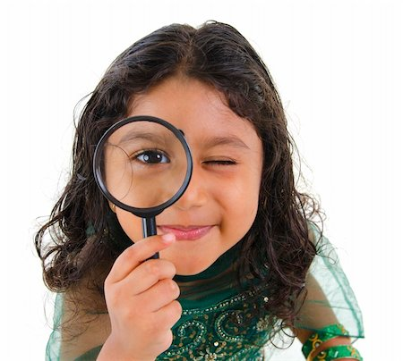 A little Indian girl peers at the camera through a magnifying glass, isolated on white background Stock Photo - Budget Royalty-Free & Subscription, Code: 400-06108512