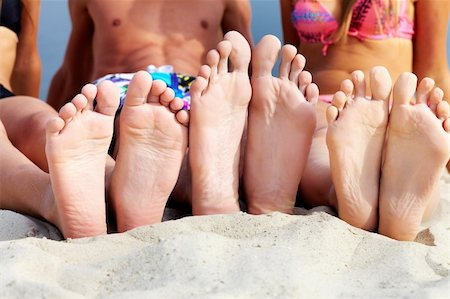 Soles of teenagers sunbathing on sandy beach Stock Photo - Budget Royalty-Free & Subscription, Code: 400-06108941