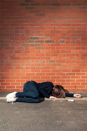 Addicted, sad young woman lying against the brick wall with syringe and cigarettes beside. Vertical. Stock Photo - Budget Royalty-Free & Subscription, Code: 400-06100323