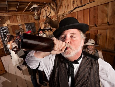 Drunken man chugs a bottle of alcohol in a saloon Stock Photo - Budget Royalty-Free & Subscription, Code: 400-06136544