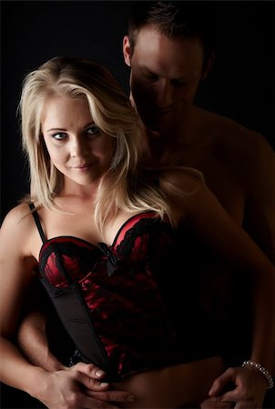 female nude sex - Young and fit caucasian adult couple in an embrace. Semi-nude and topless against a dark background with the woman wearing a sexy red and black lace corset.. Stock Photo - Budget Royalty-Free & Subscription, Code: 400-06137146
