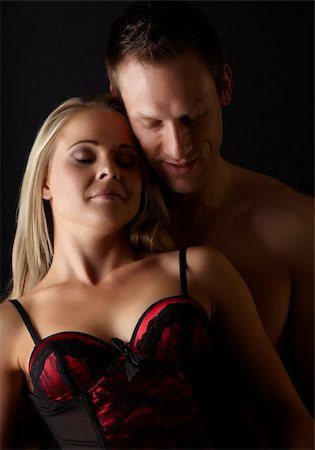 Young and fit caucasian adult couple in an embrace. Semi-nude and topless against a dark background with the woman wearing a sexy red and black lace corset.. Stock Photo - Budget Royalty-Free & Subscription, Code: 400-06137147