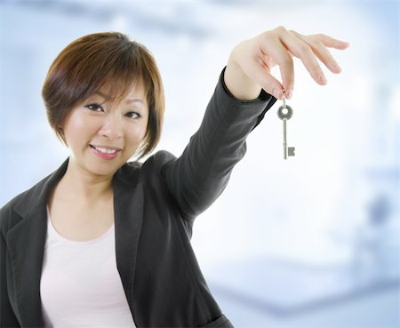 Mid adult Asian woman arms out holding a new key Stock Photo - Budget Royalty-Free & Subscription, Code: 400-06139709