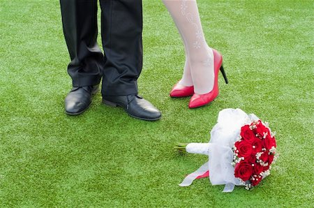 stocking feet - legs of bride and fiance on the green grass with wedding red bouquet Stock Photo - Budget Royalty-Free & Subscription, Code: 400-06142006