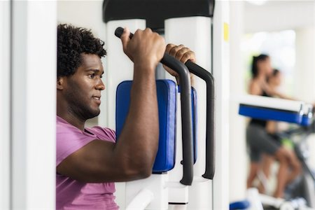 diego_cervo (artist) - Young black man exercising pectoral muscles in fitness club, with people working out on cyclette in background Stock Photo - Budget Royalty-Free & Subscription, Code: 400-06142897