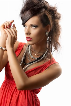 pretty brunette with fashion hair style, red dress and some necklaces, she is turned of three quarters at right, her hands are joined near the face and she looks in front of her Stock Photo - Budget Royalty-Free & Subscription, Code: 400-06174001