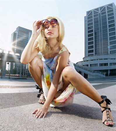 Beautiful blonde woman takes sunglasses on urban background Stock Photo - Budget Royalty-Free & Subscription, Code: 400-06205670