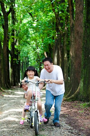 family fun day background - Father Teaching daughter  to riding bicycle Stock Photo - Budget Royalty-Free & Subscription, Code: 400-06201878