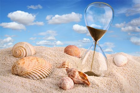 sand clock - Hourglass in the sand with blue sky Stock Photo - Budget Royalty-Free & Subscription, Code: 400-06203345