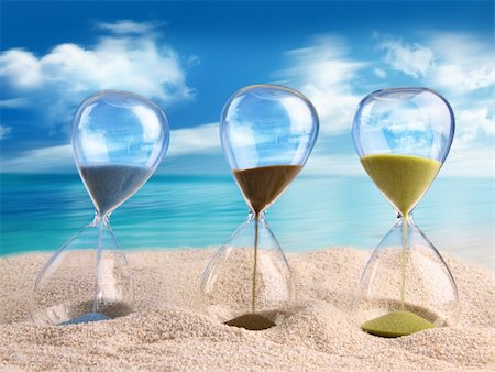 sand clock - Three hourglass in the sand with blue sky Stock Photo - Budget Royalty-Free & Subscription, Code: 400-06203367