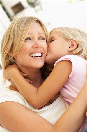 daughter kissing mother - Daughter Giving Mother Kiss Relaxing On Sofa Stock Photo - Budget Royalty-Free & Subscription, Code: 400-06203677
