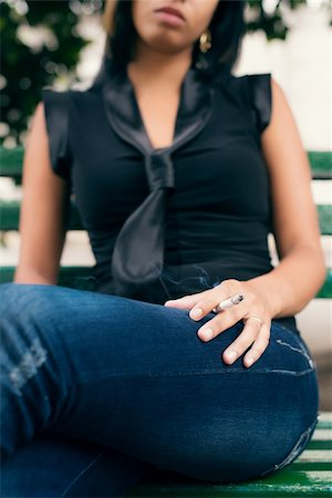 cropped view of young hispanic woman smoking cigarette while sitting on bench in city park Stock Photo - Budget Royalty-Free & Subscription, Code: 400-06333549