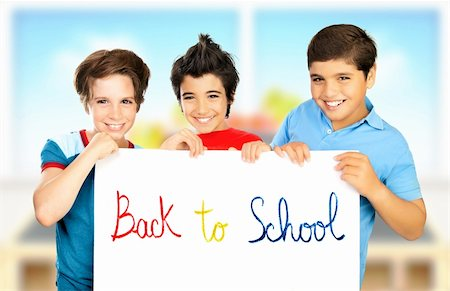 """Three classmate boys playing in classroom, best friends holding white board with phrase """"back to school"""", happy pupils having fun at school, smiling children isolated on blur colorful background Stock Photo - Budget Royalty-Free & Subscription, Code: 400-06362510"""