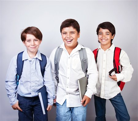 Three happy schoolboys isolated on gray&white background, back to school, best friends classmates, smiling cheerful teenagers with backpacks and books, knowledge and education concept Stock Photo - Budget Royalty-Free & Subscription, Code: 400-06362511