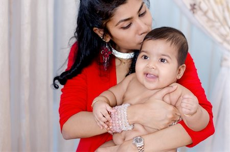 Indian mother kissing her baby girl, indoor Stock Photo - Budget Royalty-Free & Subscription, Code: 400-06389673