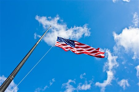 flag at half mast - American flag on a blue sky during a windy day Stock Photo - Budget Royalty-Free & Subscription, Code: 400-06389956