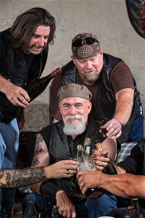 Smiling gang members toasting with bottle of liquor Stock Photo - Budget Royalty-Free & Subscription, Code: 400-06396531