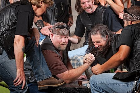 Big man in biker gang losing arm wrestling match Stock Photo - Budget Royalty-Free & Subscription, Code: 400-06396547