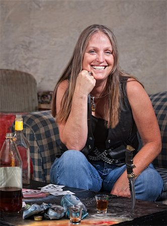 Smiling middle aged woman in leather with dagger and alcohol Stock Photo - Budget Royalty-Free & Subscription, Code: 400-06396548