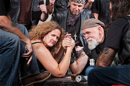 Serious woman in arm wrestling contest with biker gang Stock Photo - Budget Royalty-Free & Subscription, Code: 400-06396542